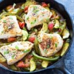 Baked chicken with zucchini, tomatoes and green peppers in a cast iron skillet.