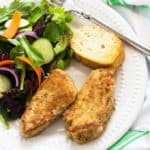 Crusted pork medallions, salad and French bread on a white plate with a fork.