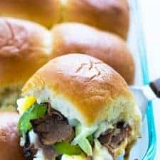 A closeup of a cheesesteak slider being removed from a baking dish with a spatula.