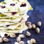 Front view of a stack of white chocolate bark with pistachios and cranberries.