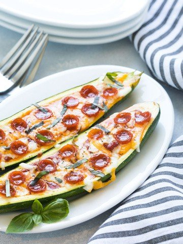Two zucchini pizza boats on an oval white plate by a striped napkin.