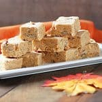 Fudge squares on a white serving tray by a decorative autumn leaf on a wood surface.