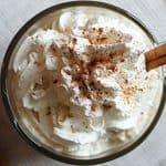 Overhead view of a coffee cocktail topped with whipped topping and ground cinnamon.