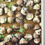 Overhead view of roasted mushrooms with rosemary in a rimmed baking sheet.
