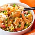A pair of chopsticks holding a shrimp in a white bowl of shrimp fried rice.