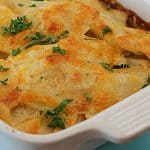 A closeup of scalloped potatoes in a white baking dish.