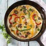 Overhead view of a frittata in a cast iron skillet by a white napkin.
