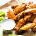 Chicken wings on brown paper by a condiment cup of ranch dressing and celery sticks.