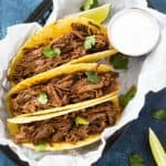 Overhead view of three hard tacos with shredded beef in a basket.