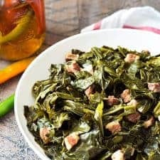 A white bowl of collards with salt pork beside a striped napkin.