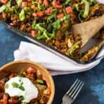 Baked taco casserole in a wooden bowl by a baking dish with casserole.