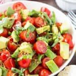 Closeup view of a salad with tomatoes, avocado and fresh basil in a white bowl.