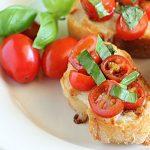 Three slices of tomato bruschetta on a white plate.