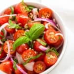 Overhead closeup of a tomato salad with basil and red onions in a white bowl.