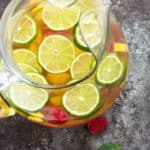 Overhead view of a glass pitcher of sangria with sliced limes, mango and raspberries.