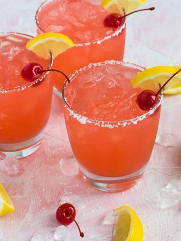 Three margaritas in salt-rimmed glasses garnished with cherries and lemon.