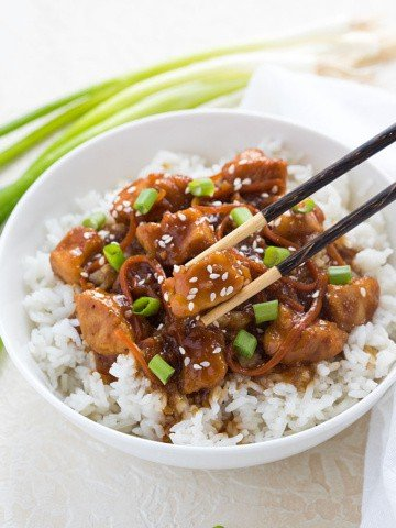 Mongolian chicken topped with green onions over rice in a  bowl with a pair of chopsticks.