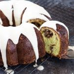 A slice of cake being removed from a bundt cake on a cooling rack.