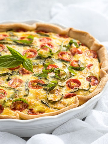 Front view of a quiche with tomatoes and basil in a white pie dish.