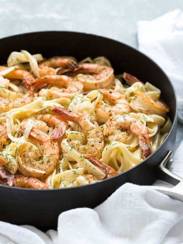 Creamy fettuccine with shrimp and dill in a skillet.