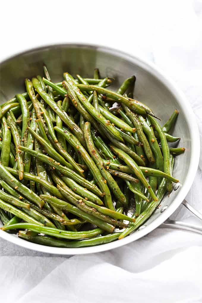 Overhead view of cooked green string beans with garlic in a skillet.