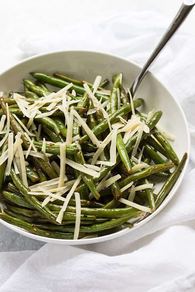 Green beans topped with grated Parmesan cheese in a white bowl with a spoon.
