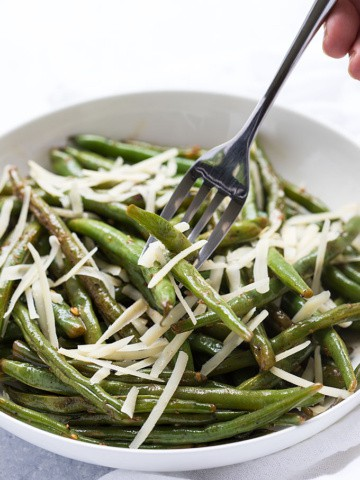 A fork piercing garlic green beans with cheese in a white bowl.