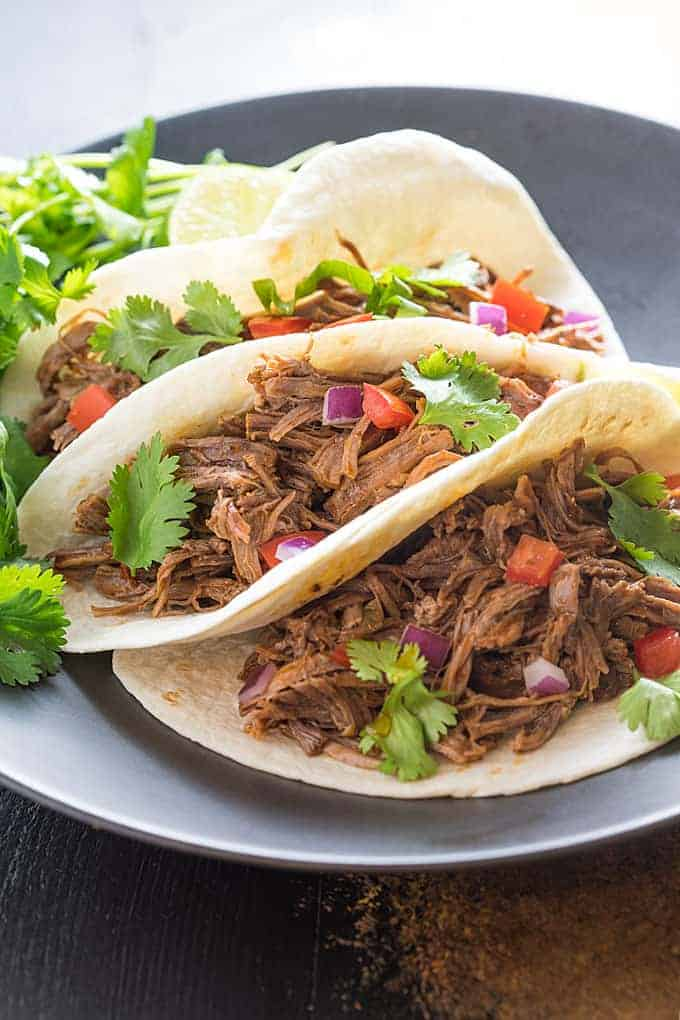 A closeup of three shredded beef soft tacos on a black plate.