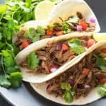 A closeup of three soft tacos with Mexican shredded beef on a black plate with cilantro.
