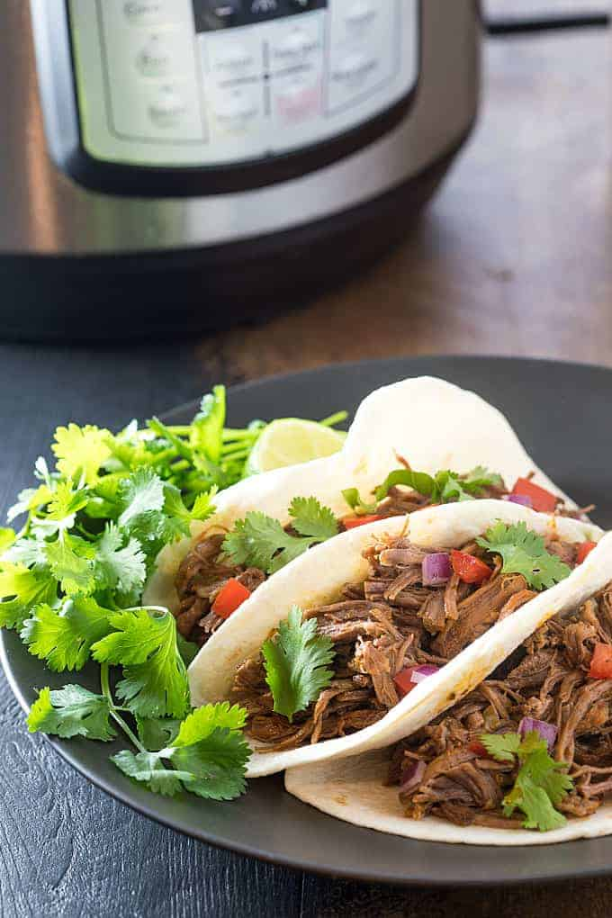 Three soft tacos with shredded beef on a plate. An Instant Pot is in the background.
