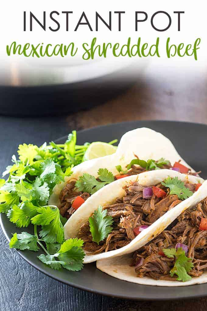 Three tacos with Mexican shredded beef on a black plate. Overlay text at top of image.