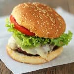 Front view of a cheeseburger with lettuce and tomato on a sheet of parchment paper.