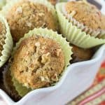 A closeup of muffins in yellow muffin liners in a square white bowl.