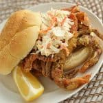 A fried soft shell crab sandwich with coleslaw on a white plate with a lemon wedge.