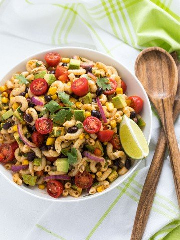 Overhead view of pasta salad with black beans, corn, avocado and tomatoes in a white bowl.