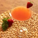 A martini garnished with a strawberry on a straw place mat.