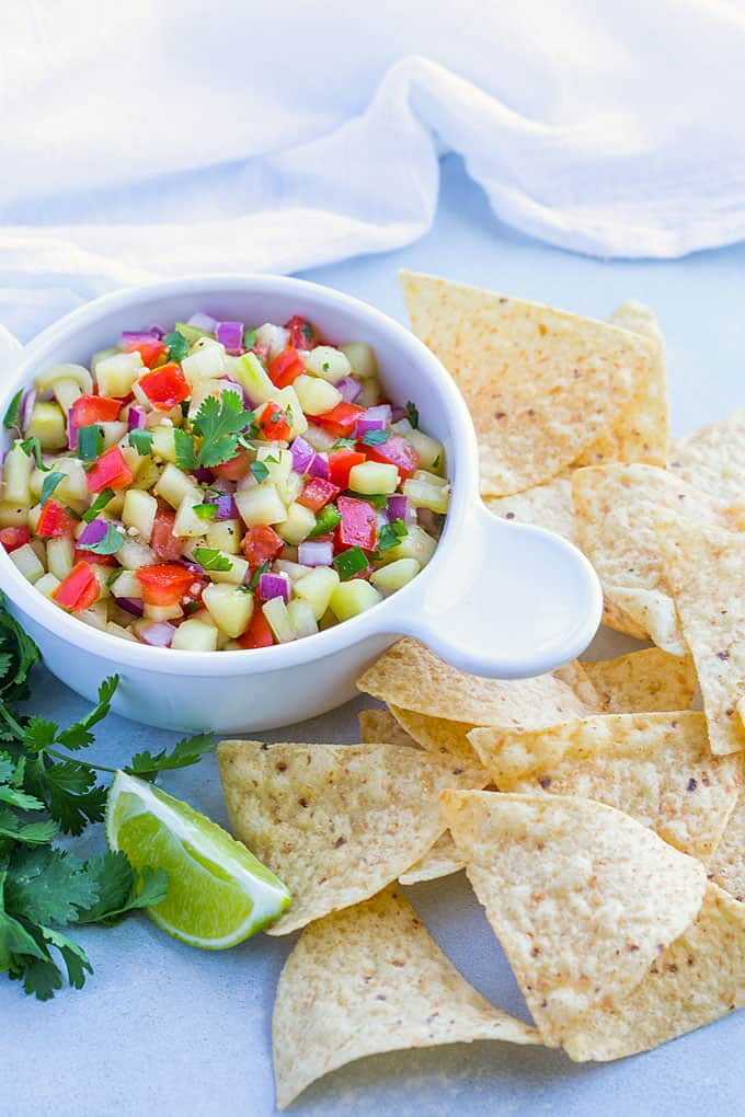 Salsa with cucumbers, tomatoes and onion in a white bowl beside tortilla chips.