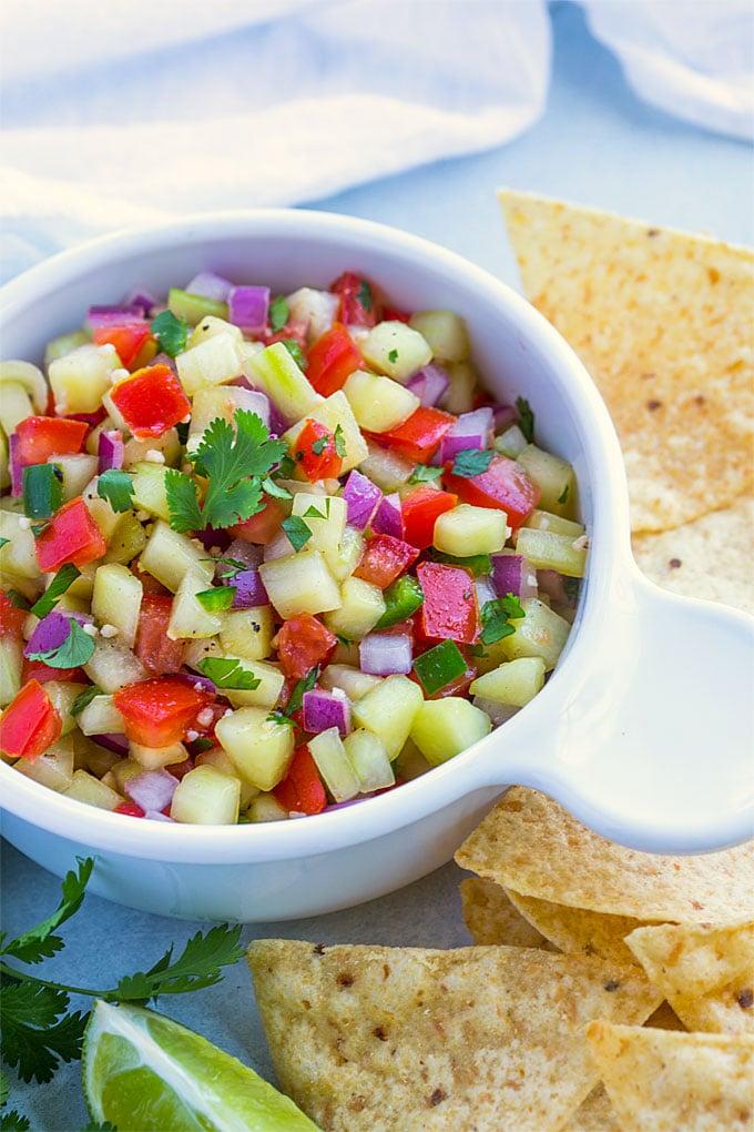 Closeup view of cucumber salsa in a white bowl beside tortilla chips.