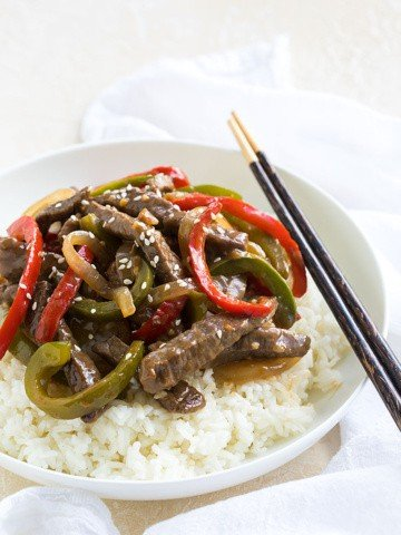 Pepper steak over rice in a white bowl with a pair of brown chopsticks.