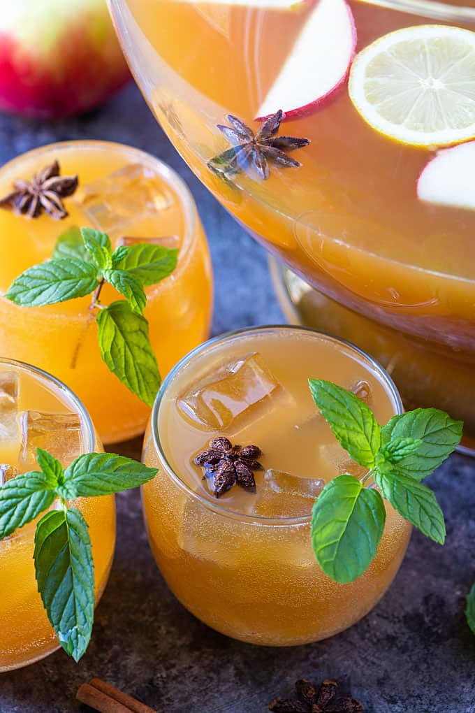 Overhead closeup of three glasses of punch garnished with mint and star anise.