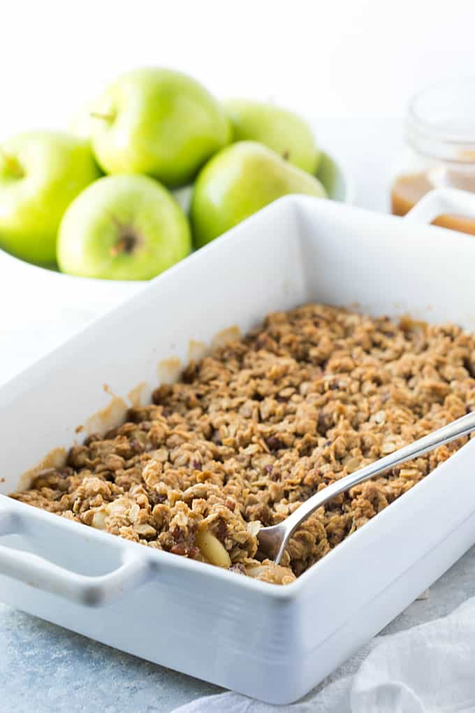 Apple crisp in a white baking dish with a serving spoon.