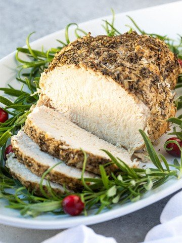 A sliced turkey breast garnished with rosemary and cranberries on a white platter.