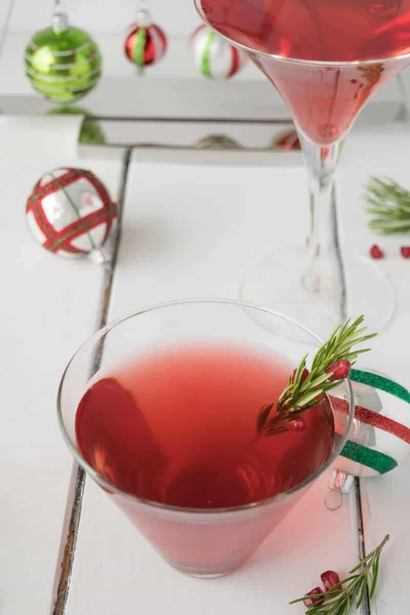 A cosmopolitan cocktail in a glass garnished with rosemary and pomegranates on a white surface.