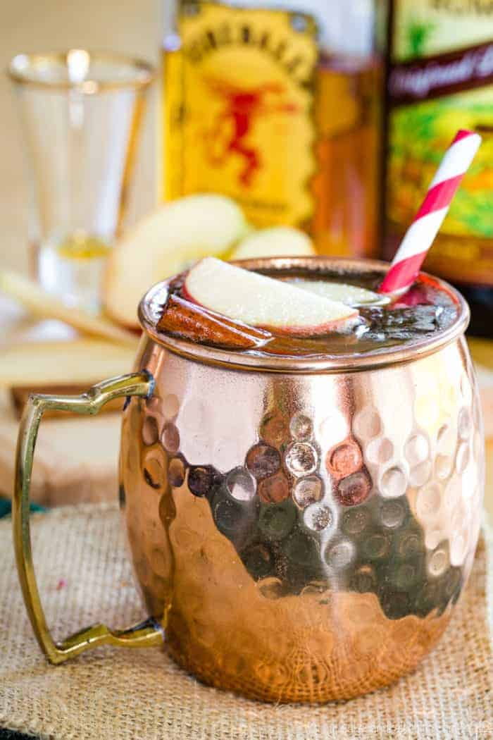 A moscow mule with sliced apple and cinnamon stick in a copper mug with a straw.