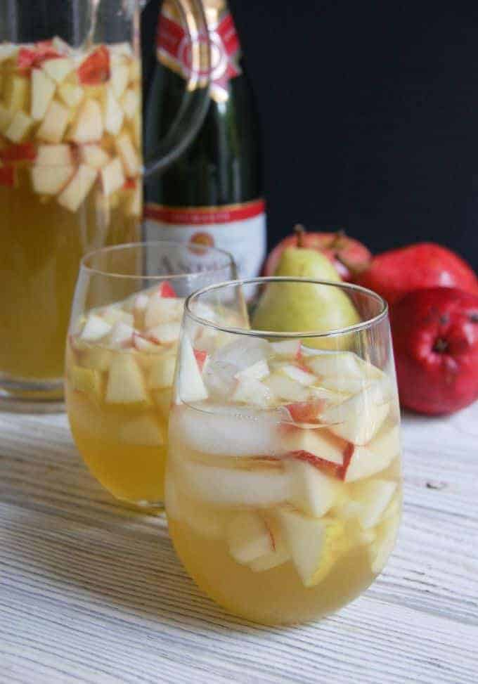 Two glasses of sangria with ice, chopped apples and pears.