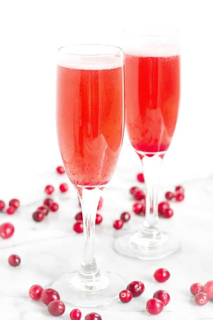 Two cranberry sparkling wine cocktails in champagne flutes on a white surface with cranberries.