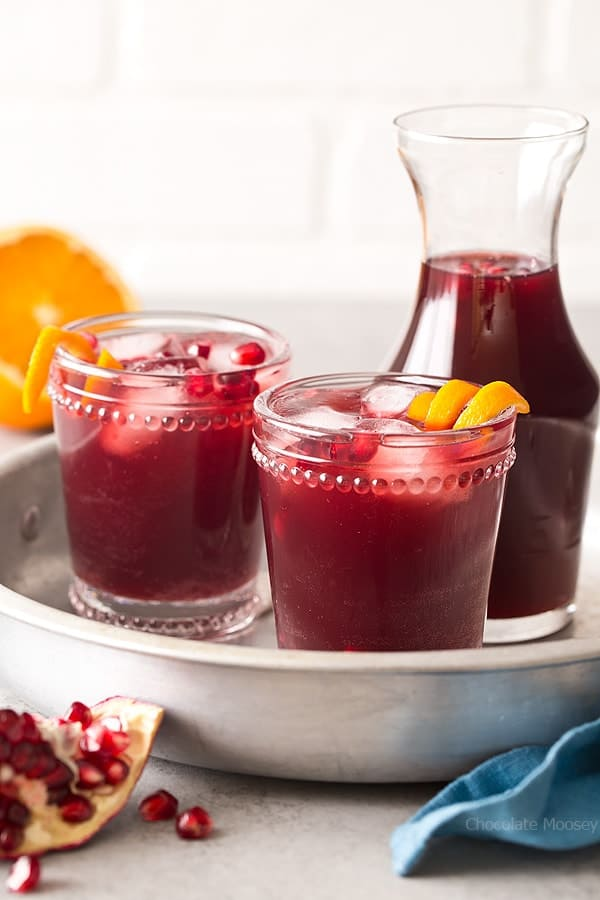 Two glasses of punch with pomegranates and orange slices on a silver serving tray.