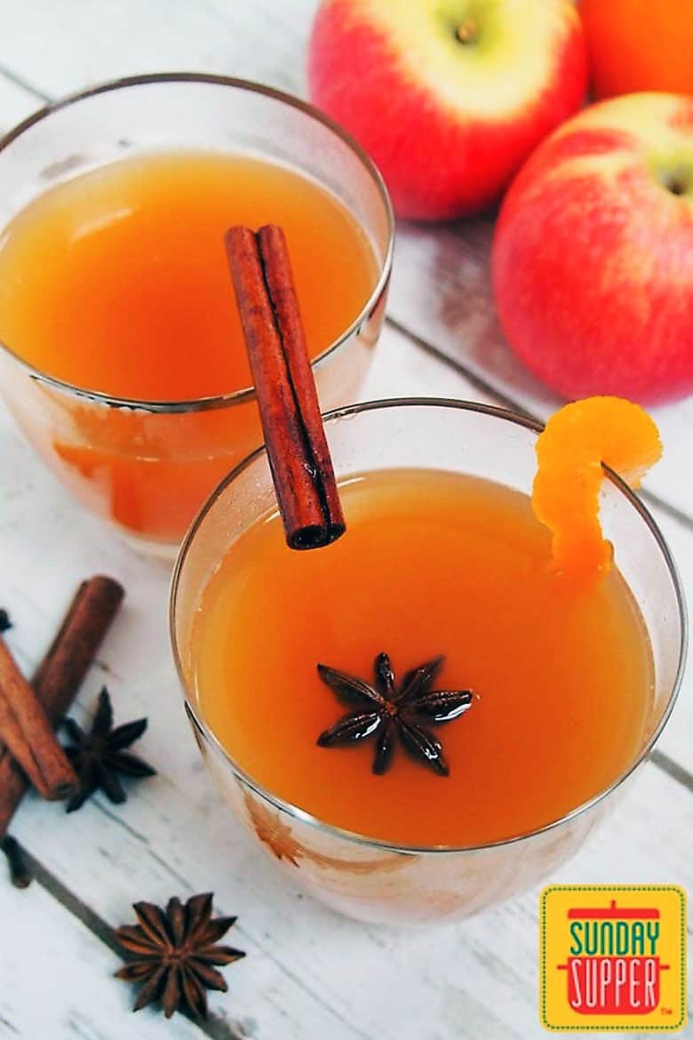 Overhead view of an apple cider cocktail garnished with star anise and a cinnamon stick.