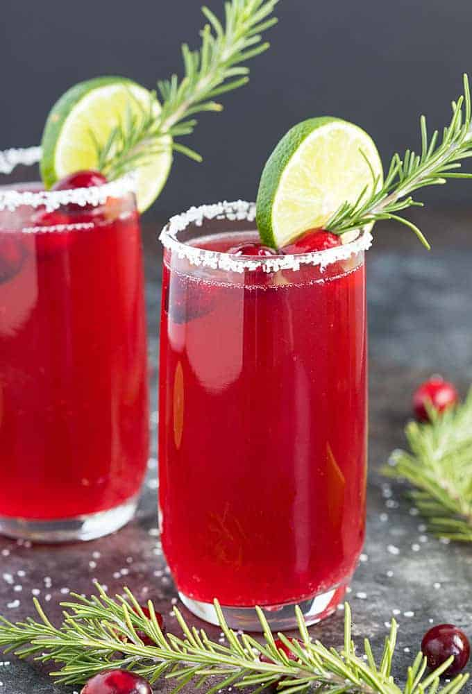 Two salt-rimmed glasses of mimosa margaritas garnished with lime, cranberries and rosemary.