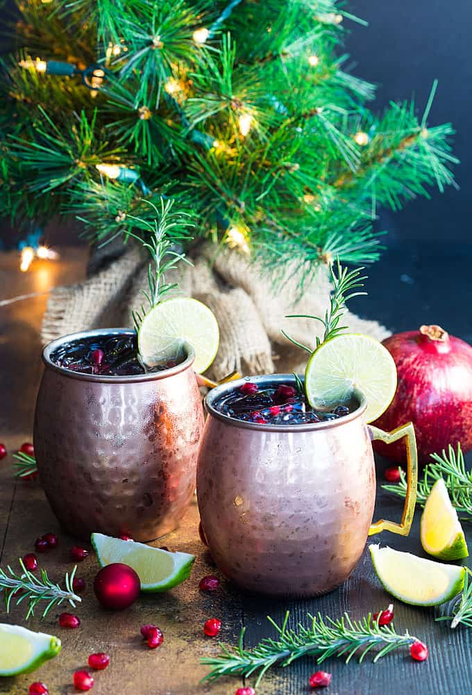 Two moscow mules garnished with pomegranates and lime in copper mugs by a small holiday tree.